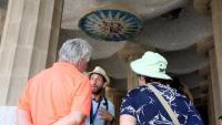 Un guia turístic donant explicacions a un grup de persones a la sala Hipòstila del Park Güell