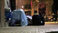 Dos voluntaris d'Arrels Fundació parlen amb una dona que dorm al carrer aquest dijous a la nit