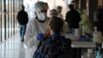 Una sanitària fa una prova a un home a Banyoles