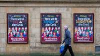 Un vianant passa per davant d'uns cartells al·lusius a la Covid-19, al centre de Glasgow