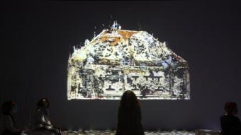 Un grup de persones contemplen en una pantalla una de les peces digitalitzades