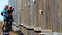 Operaris treballant en un segment de mur de metall amb Mèxic, a l'estat nord-americà de Nou Mèxic