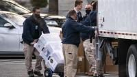 Un operari trasllada caixes plenes de diaris al camió amb les pertinences de Donald Trump