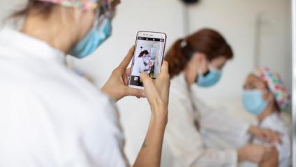 Una infermera de l'Hospital de Sant Pau posa una vacuna a una companya, mentre una altra li fa una foto