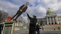 Un home anti-Trump amb una estàtua falsa del president al davant del Capitoli de l'Estat de Pennsilvània, a Harrisburg