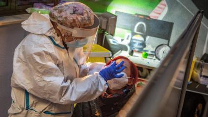 Una sanitària fa un prova PCR a una dona a Barcelona