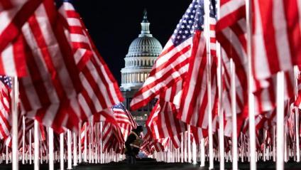 Una persona passa entre les banderes posades davant del Capitoli