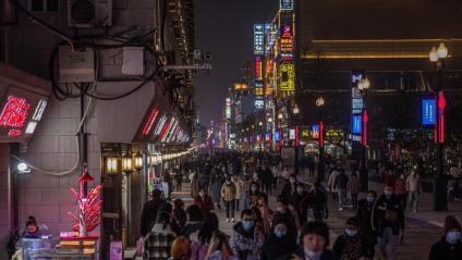 Gent amb mascareta camina per un carrer comercial de Wuhan