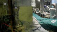 Una professional sanitària atén un malalt de Covid-19 a una UCI del Clínic