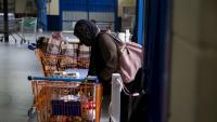 Una dona recull els aliments en un dels centres de distribució a Girona