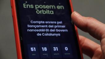Un telèfon mòbil amb el compte enrere del llançament del primer nanosatèl·lit del Govern