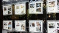 Imatge d'ofertes de compravenda d'habitatges a l'aparador d'una agència immobiliària