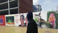 Un jove mira el mural fet per Roc Blakbloc, ahir al matí, després que uns desconeguts el desfiguressin pintant-hi a sobre amb esprais