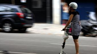 Una veïna de Barcelona transitant pel centre de la ciutat amb el seu patinet