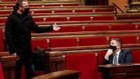 El diputat de la CUP Vidal Aragonès conversa amb el conseller d'Interior, Miquel Sàmper, abans de començar el ple