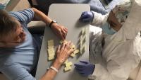Un resident juga al dominó amb una infermera durant el confinament