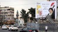 Una tanca publicitària amb fotos de Francesc i el gran aiatol·là Ali al-Sistani, a Bagdad