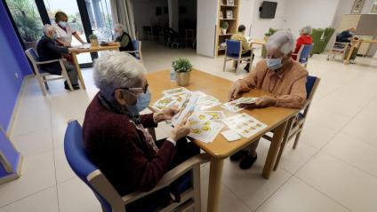 Els residents fent jocs de taula en grups reduïts i taules separades a la residència Vitalia de Sants