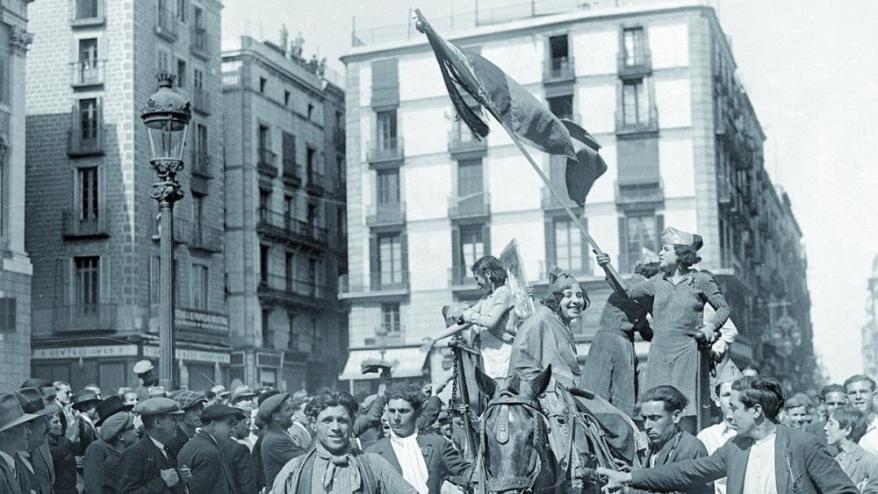 <b>A la plaça de Sant Jaume</b> diverses dones, amb el barret frigi i amb una bandera republicana, participen en la festa amb motiu de la proclamació de la República <b>TITOLET </b>Text