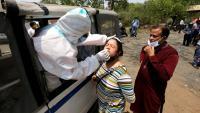 Un sanitari fa una prova a una dona índia per saber si ha contret la Covid a Bohal