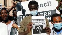 Un jove mostra un cartell en què es reclama la regularització de les persones migrades en situació irregular, el 20 de juny de 2020