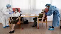 Vacunació en una llar d'avis de València. A baix, el llibre del periodista Manuel Rico, que investiga sobre el negoci dels geriàtrics