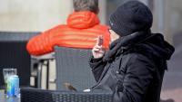 Una dona fumant a la terrassa d'un bar