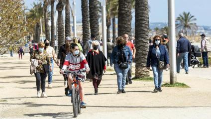Gent passejant al costat del mar