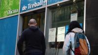 Dues persones esperant per entrar a l'Oficina de Treball del carrer Sepúlveda de Barcelona