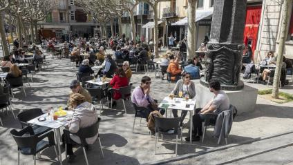 Terrasses en una plaça de Mataró amb diferents grups de gent asseguda a les taules