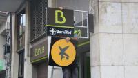 ÇUn operari canviant el logotip de Bankia pel de CaixaBank a un oficina de la Rambla del Poblenou de Barcelona