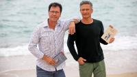Eduard Planas i Krzysztof Charamsa a la platja de Badalona, amb el llibre que acaben de publicar en català i en castellà