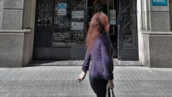 Una ciutadana passa pel davant de l'entrada de la Sindicatura, a la ronda de Sant Pau