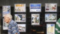 Una persona passa per davant d'anuncis de pisos en una immobiliària