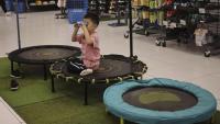 Un nen, sol, jugant en una botiga d'articles esportius a la ciutat de Pequín, dilluns