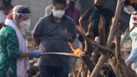 Una dona fa els últims ritus d'una víctima de la Covid-19 en un crematori, a Nova Delhi (Índia)