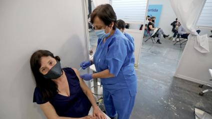 Una dona rebent una dosi de la vacuna contra la Covid al gran espai de vacunació que hi ha a la fira de Montjuïc