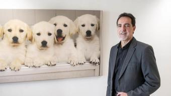 Botí, a la seu de l'ONCE al carrer Sepúlveda de Barcelona, amb una fotografia dels cadells de gossos pigall que s'ensinistren per acompanyar-los