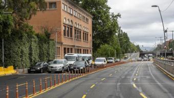 Vehicles  al davant de la façana de l'escola Casas, que dona a una autopista urbana