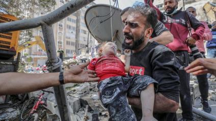 Un pare porta el seu fill mort, recuperat de les runes de l'edifici esfondrat per míssils israelians