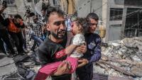 Un pare treu la seva filla ferida de casa, destruïda per un bombardeig a Gaza