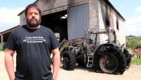 L'Abel davant d'un tractor cremat i del cobert de la seva granja on es va produir l'incendi