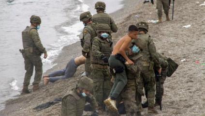 Membres de l'exèrcit espanyol ajuden alguns dels migrants que han aconseguit creuar els espigons fronterers de Ceuta