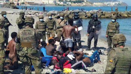 Policies espanyols vigilen la tanca de Ceuta. A sota, militars amb immigrants que han aconseguit entrar
