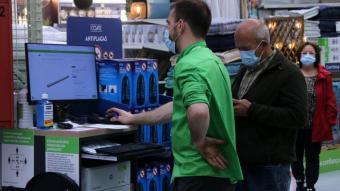 Un treballador atenent un client l'establiment de Leroy Merlin a Tortosa