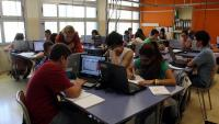 Imatge d'arxiu d'una aula amb estudiants treballant amb ordinadors