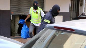 Agents dels Mossos d'Esquadra sortint carregats de bosses d'un bar de Gavà