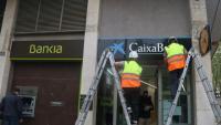 Dos operaris canviant la marca d'una oficina de Bankia per CaixaBank