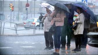 Un grup de persones espera a travessar un carrer