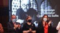 El periodista Josep Cuní, Mari Carmen Bellver –vídua de l'escriptor– i l'alcaldessa Ada Colau durant l'homenatge a l'autor de 'L'ombra del vent'
